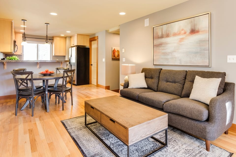 open concept room with gray couch and brown table