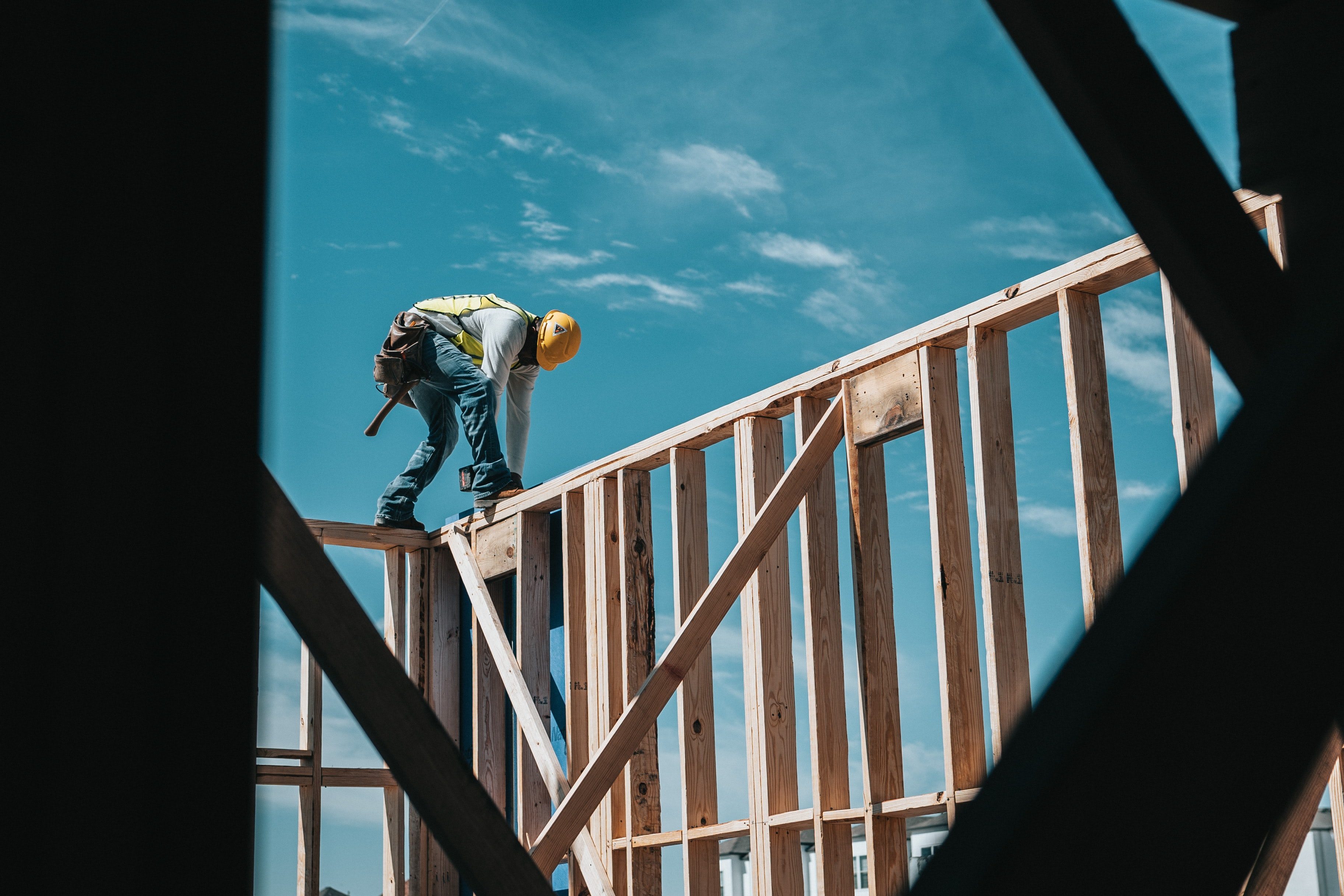 man-working-wood-framed-house